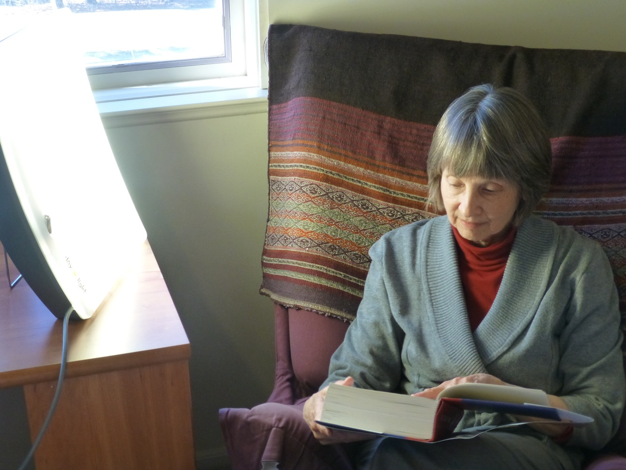 Lois Maharg sits next to a light box, reading a book